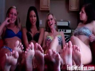 Quatro meninas que fazem exame de seu céu do fetiche do pé