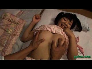 Menina asiática, tocando dedo com o galo no colchão no quarto