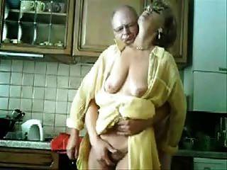 Mamã e paizinho que têm o divertimento na cozinha.Vídeo roubado