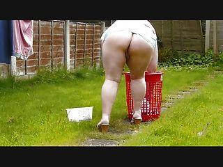 Amanhecer pendura para fora a lavagem vestindo uma saia muito curta