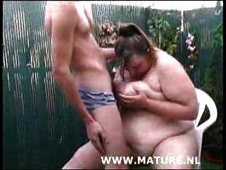 Cadela gorda chupando galo no jardim e recebendo seus peitos creamed