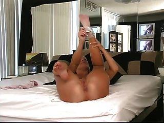 Loira fica de joelhos na cama para mostrar seu burro redondo
