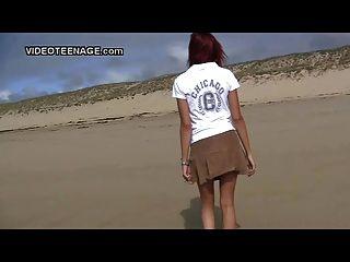 Adolescente nudista piscando na praia