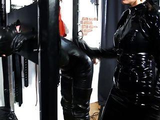 Uma domina de vinil chicoteia seu escravo