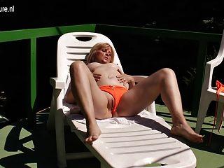 Velha, mas ainda mamãe slut masturbando-se ao sol