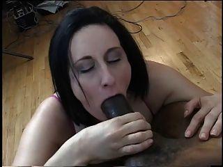 Morena com grandes mamas suga em um enorme galo preto em seus joelhos