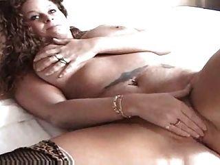 Sexy ruiva brincando com seu bichano na cama