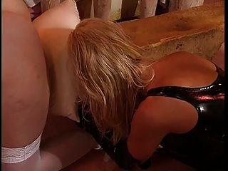 Tetas grandes, amante de lésbica vestida de couro desfrutando com seu escravo