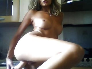 Menina italiana com brinquedos sexuais na cozinha
