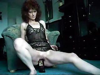 Senhora madura engole uma garrafa de uísque