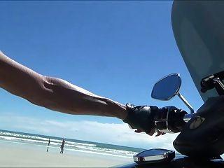 Motociclista de couro sexy na coxa botas na praia