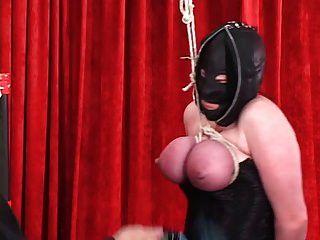 A mulher encadernada corseed no capuz de couro obtém tetas amarradas para que elas se tornem vermelhas
