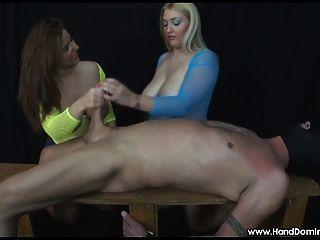 2 garotas com mamas enormes examinam um galo durante a mão feminina