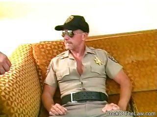 um policial mais velho chupa um urso corpulento