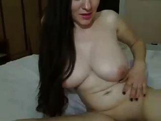 Longa menina de cabelo escuro, mamas grandes na cama acanhando bichano