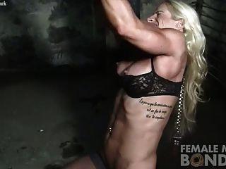 Bodybuilder feminino em cadeias na masmorra