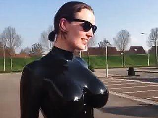 Peitos grandes em catsuit de látex brilhante