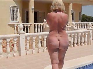 uma mulher madura com uma bunda redonda nua caminha à beira da piscina